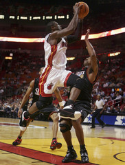 Miami Heat guard Dwyane Wade shoots against Kevin Ollie of the Philadelphia Sixers during NBA basketball action in Miami, Florida