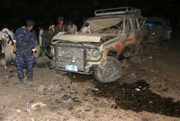 Soldiers and tribal men gather at the site of a suspected al-Qaeda car bomb attack in the Yemeni province of Marib