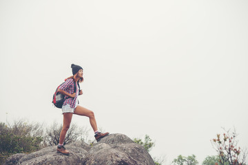 Hiker with backpacks standing on top of a mountain and enjoying nature view.