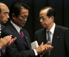 Aso, secretary-general of Japan's ruling LDP, claps his hands as outgoing Japanese PM Fukuda leaves the LDP parliamentarian meeting in Tokyo