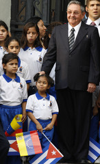 Cuban President Raul Castro stands next to children as he visits the tomb of Simon Bolivar at the national cemetery in Caracas