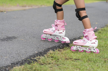 Little girl with rollerblades in park