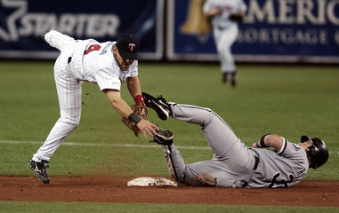 Twins second baseman Ojeda jumps to avoid sliding White Sox player Rowand on a double play.