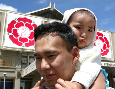 MAN CARRING HIS SON STANDS IN FRONT OF THE LOGOS OF MONGOLIAN PEOPLE'S REVOLUTIONARY PARTY IN ULAN ...