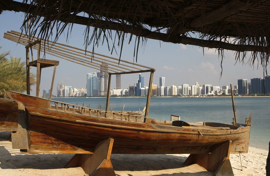 A view of the Abu Dhabi skyline is seen past a boat on a beach