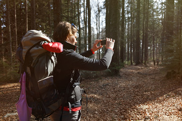 Hiker taking photographs on her hike through the woods