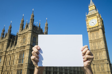 Hands holding blank sign in front of the Houses of Parliament at Westminster Palace under bright blue sky in London, England