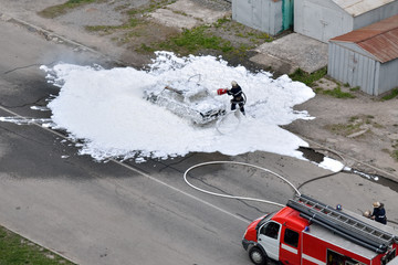 Firefighters are extinguished by a foam burning car. The work of special rescue services.