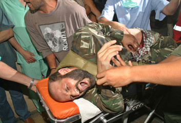 PALESTINIAN CARRY A WOUNDED YOUTH AFTER ISRAELI RAID IN GAZA.