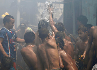 Residents cool themselves from a broken pipe after a fire razed a squatter colony in Manila