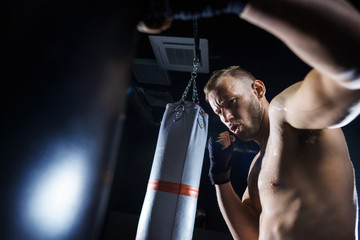Male boxer fighting in the gym studio .