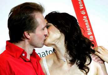 Actress Rachel Weisz kisses actor Ralph Fiennes as they attend a photocall in Venice.