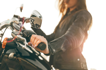 Girl on a motorcycle. She is beautiful, posing on a motorcycle at sunset