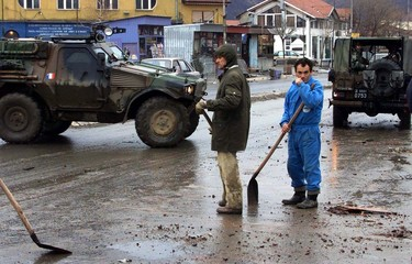 STREET CLEANERS STAND NEXT TO THE FRENCH KFOR APC IN THE TOWN OF KOSOVSKA MITROVICA.