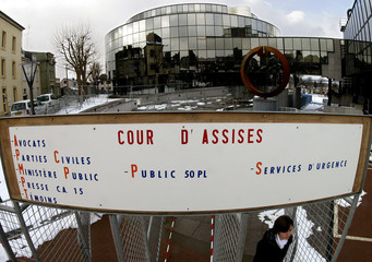 A woman walks past the entrance of the security zone outside the Arlon courthouse  February 28, 2004..