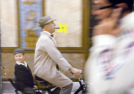 A man walks past a poster showing character Mr. Hulot played by French actor/director Jacques Tati, smoking a windmill toy which replaces his emblematic pipe, in the metro in Paris