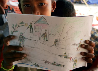 An Acehnese child Yuliandi Saputra shows his drawing of a conflict scene between Aceh rebels and the..