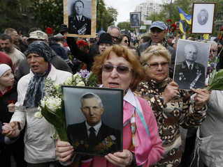 People hold pictures of World War Two soldiers as they take part in Immortal Regiment march during Victory Day celebrations in Kiev