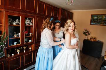 Bridesmaids and bride preparing at room on wedding morning.