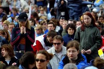 Mourners outside Rome's Colosseum watch the funeral of the late Pope John Paul II being televised ...
