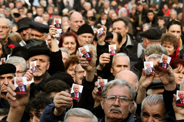 Supporters of Slobodan Milosevic hold up pictures of the former Serbian president  in Belgrade