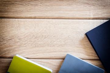 Drei Bücher auf Holz Hintergrund