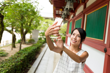 Young Woman taking selfie by mobile phone in japanese temple