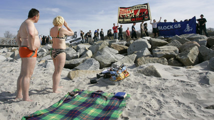 Tourists take pictures as protestors carrying banners walk past at a beach at the Baltic Sea resort of Heiligendamm