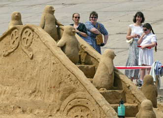 UKRAINIANS LOOK AT A SAND SCULPTURE OF PENGUINS RUNNING OVER A BRIDGE IN KIEV.