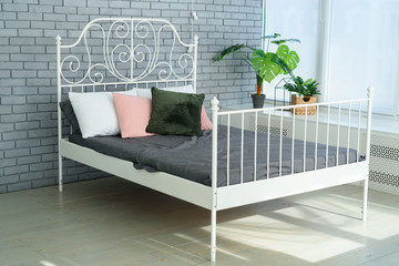 Large white metal frame bed with decorative metal headboard and white, pink and green pillows on it. Feminine bedroom with grey brick wall and white metal bed