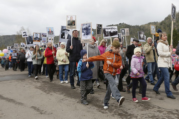 People carry pictures of World War Two soldiers as they take part in Immortal Regiment march during Victory Day celebrations, marking 72nd anniversary of victory over Nazi Germany in World War Two, in Divnogorsk