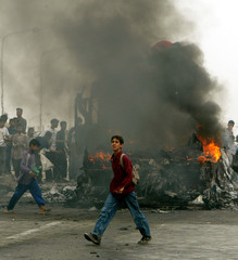 IRAQI YOUTHS WALK PAST WRECKAGE OF OIL TANKER IN BAGHDAD.