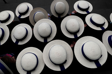 Pupils wearing boater hats as part of their school uniform pose for a group picture outside the V & A museum in London