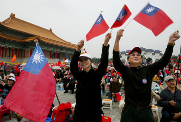 SUPPORTERS HOLD NATIONAL FLAGS AT THE CHIANG KAI SHEK MEMORIAL HALL IN TAIPEI.