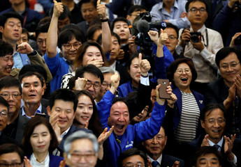 Party members of the Democratic Party of Korea react as they watch a television report on an exit poll of the presidential election in Seoul