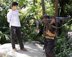 A Cambodian man watches a soldier from Thailand in the Preah Vihaer temple compound