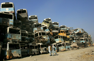 Afghan men walk in front of pile of scrapped buses in Kabul