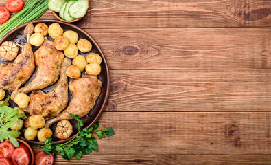 Chicken legs with baked potatoes and vegetables on wooden background.