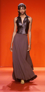 A model in a brown leather sleeveless vest and brown full length skirt walks the runway at the Dougl..