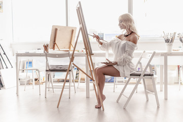 Inspired by the artist sitting in his bright Studio and paints with a brush on the easel