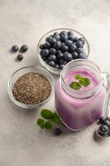 Blueberry smoothie with chia seeds in glass jar on grey concrete background, selective focus