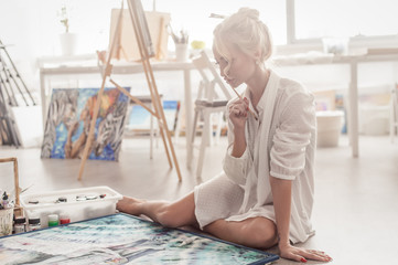 Beautiful young woman sitting on the floor in a bright Studio and paints with paint on canvas.