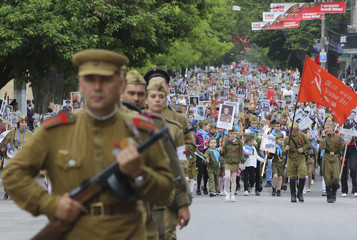 People carry pictures of World War Two soldiers as they take part in Immortal Regiment march during Victory Day celebrations in Simferopol