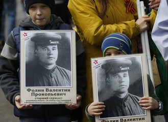 Children hold pictures of World War Two soldiers as they take part in Immortal Regiment march during Victory Day celebrations, marking 72nd anniversary of victory over Nazi Germany in World War Two, in Divnogorsk