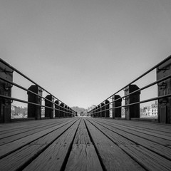 Low angle view of a wooden pier stretching out into the distance. Black and white process with added grain texture and copy space.