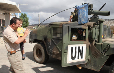 Man with his child waves to Spanish UN soldiers as they patrol Houla village in south Lebanon
