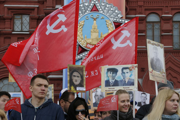 People hold flags and pictures of World War Two soldiers before Immortal Regiment march during Victory Day celebrations, marking 72nd anniversary of victory over Nazi Germany in World War Two, at Red Square in Moscow