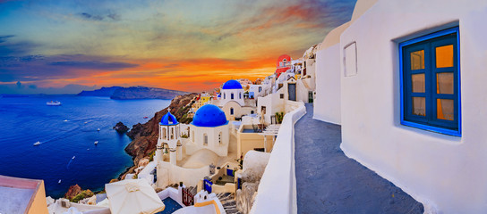 Self adhesive Wall Murals Santorini Amazing wide panorama sunset view with white houses on church with blue roofs in Oia village on Santorini island in Greece.