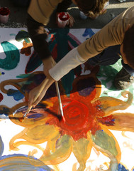 Children paint flowers on the world's longest painting ever made by children, in Bucharest