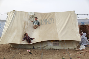 Internally displaced siblings from Swat play on top their family tent at the UNHCR Yar Hussain camp in Swabi district